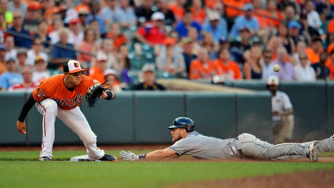 Tampa Bay Rays shortstop Ben Zobrist slides into third base safely after hitting a triple in the ninth inning as Baltimore Orioles third baseman Manny Machado does not get the throw in time.