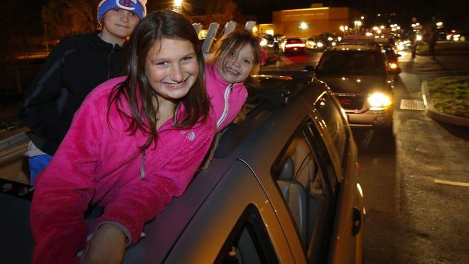 Layla, Joshua and Emma Sosner of Jackson wait for the start of the annual Marlboro car menorah parade Monday evening.