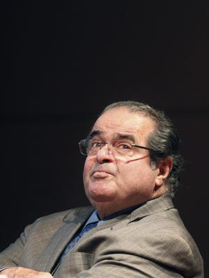 In this Oct. 18, 2011, file photo, U.S. Supreme Court Justice Antonin Scalia looks into the balcony before addressing the Chicago-Kent College Law justice in Chicago. On Saturday,  the U.S. Marshals Service confirmed that Scalia has died at the age of 79.