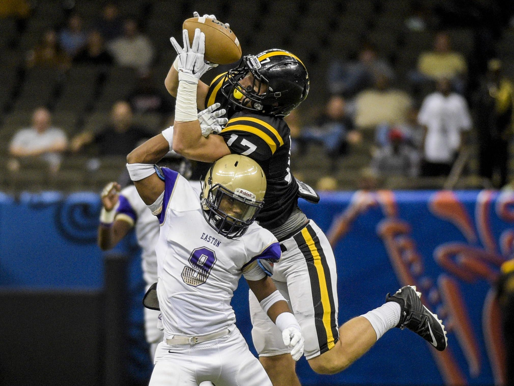 Neville wide receiver Chris Fuller (17) makes a catch over a Warren Easton defender during the 2014 Class 4A state championship game.