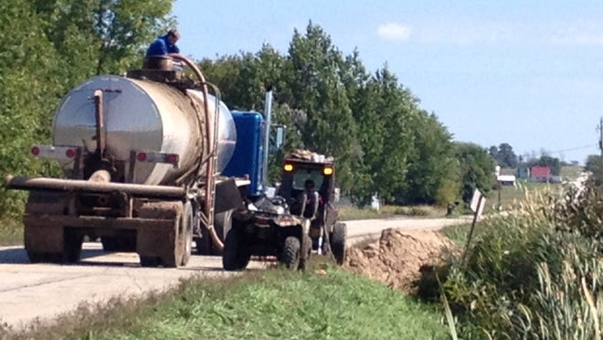 Contractors transfer spilled manure into waiting trucks Wednesday.