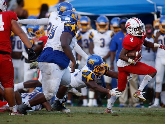 Leon's Queze Brutton shakes off a Raider during the Lions' game against Rickards at Cox stadium Friday.