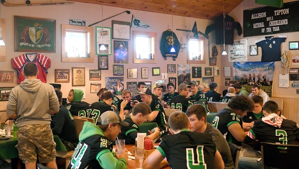 Players on the Mountain Heritage football team wait