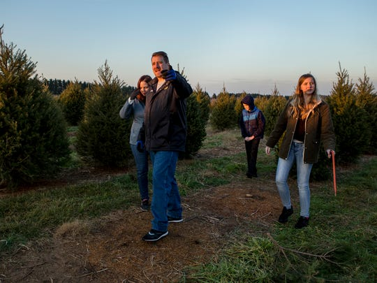 Tom Garrett points a Christmas tree out to his wife Alice as they walk with their children through the trees at Coleman's Christmas Tree Farm in Middletown on Wednesday afternoon.