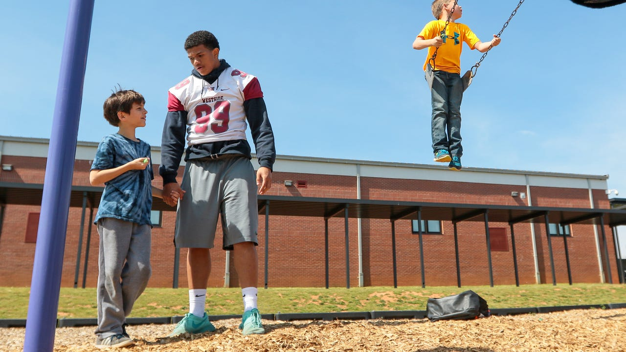 Westside High School football players Dionte Osbey and Lummie Young visit Nathan Johnson, 8, of Centerville Elementary, where he had been bullied by classmates. They all learn school is good, bullying is not, and each person is different.