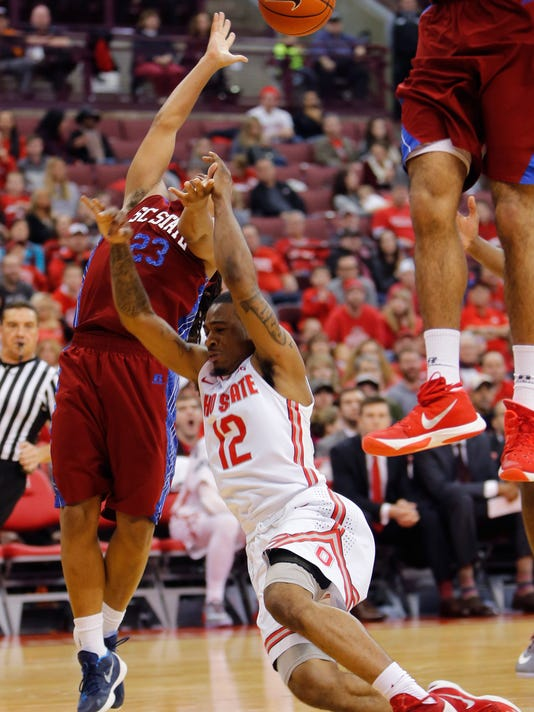 South Carolina State's Ty Soloman, left, fouls Ohio State's A.J. Harris as he tries to shoot during the second half of an NCAA college basketball game Sunday, Dec. 27, 2015, in Columbus, Ohio. Ohio State beat South Carolina State 73-57. (AP Photo/Jay LaPrete)
