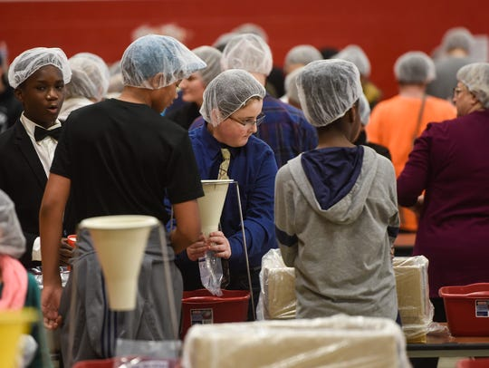 People gather to package meals for famine victims as