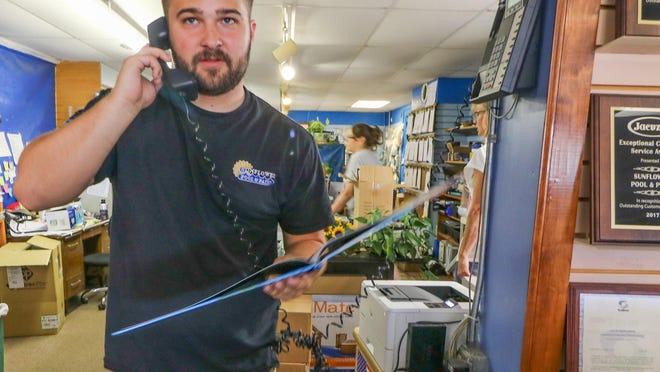 Corbin Munson, 3D designer and estimator at Sunflower Pool & Patio, answers a phone call from a customer on Tuesday. Munson's hours have increased because of the increase in sales and demand for in-ground pools.