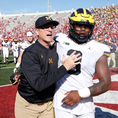 Jim Harbaugh celebrates with Rashan Gary after the