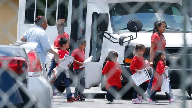 Migrant children walk off a bus at the Catholic Charities' Msgr. Bryan Walsh Children's Village in Cutler Bay, Fla., on Jan. 21.