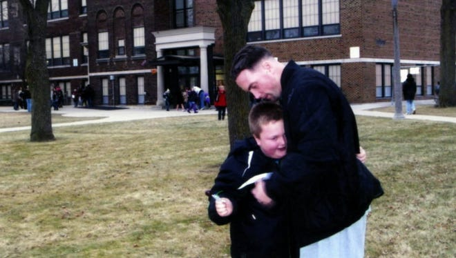 Jeremy Cunningham, who died at the Milwaukee Secure Detention Facility in 2011, hugs his now 15-year-old son at the boy's school. When Cunningham had a violent seizure and his cellmate hit the emergency alarm, a guard ignored the cellmate's pleas.