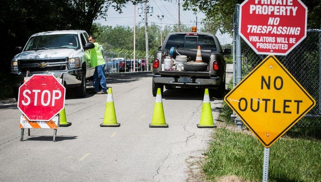 Muncie Sanitary District workers set up a roadblock Thursday on the drive to MSD offices along Kilgore Avenue. The district set up the roadblock after the FBI raided their offices.