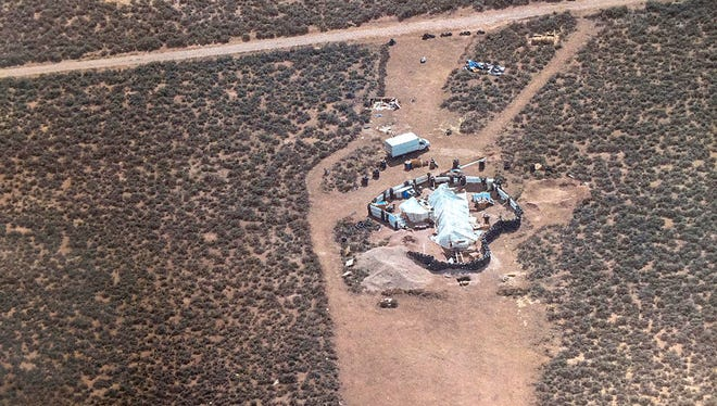 This Friday, Aug. 3, 2018, aerial photo released by Taos County Sheriff's Office shows a rural compound during an unsuccessful search for a missing 3-year-old boy in Amalia, N.M. Law enforcement officers searching the compound for the missing child didn't locate him but found 11 other children in filthy conditions and hardly any food, a sheriff said Saturday. The children ranging in age from 1 to 15 were removed from the compound and turned over to state child-welfare workers, Taos County Sheriff Jerry Hogrefe said.in Taos.