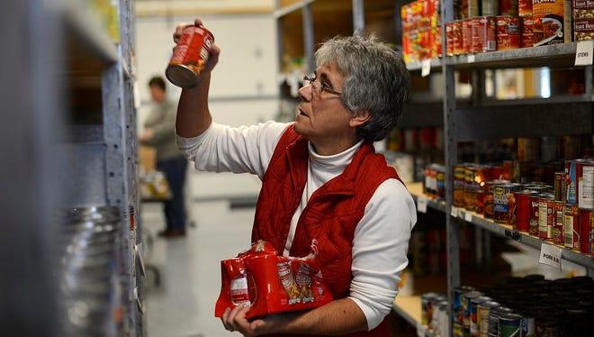 Volunteer Joan Van Grunsven puts away canned goods inside the De Pere Christian Outreach Food Pantry in De Pere on Wednesday, Nov. 5, 2014.