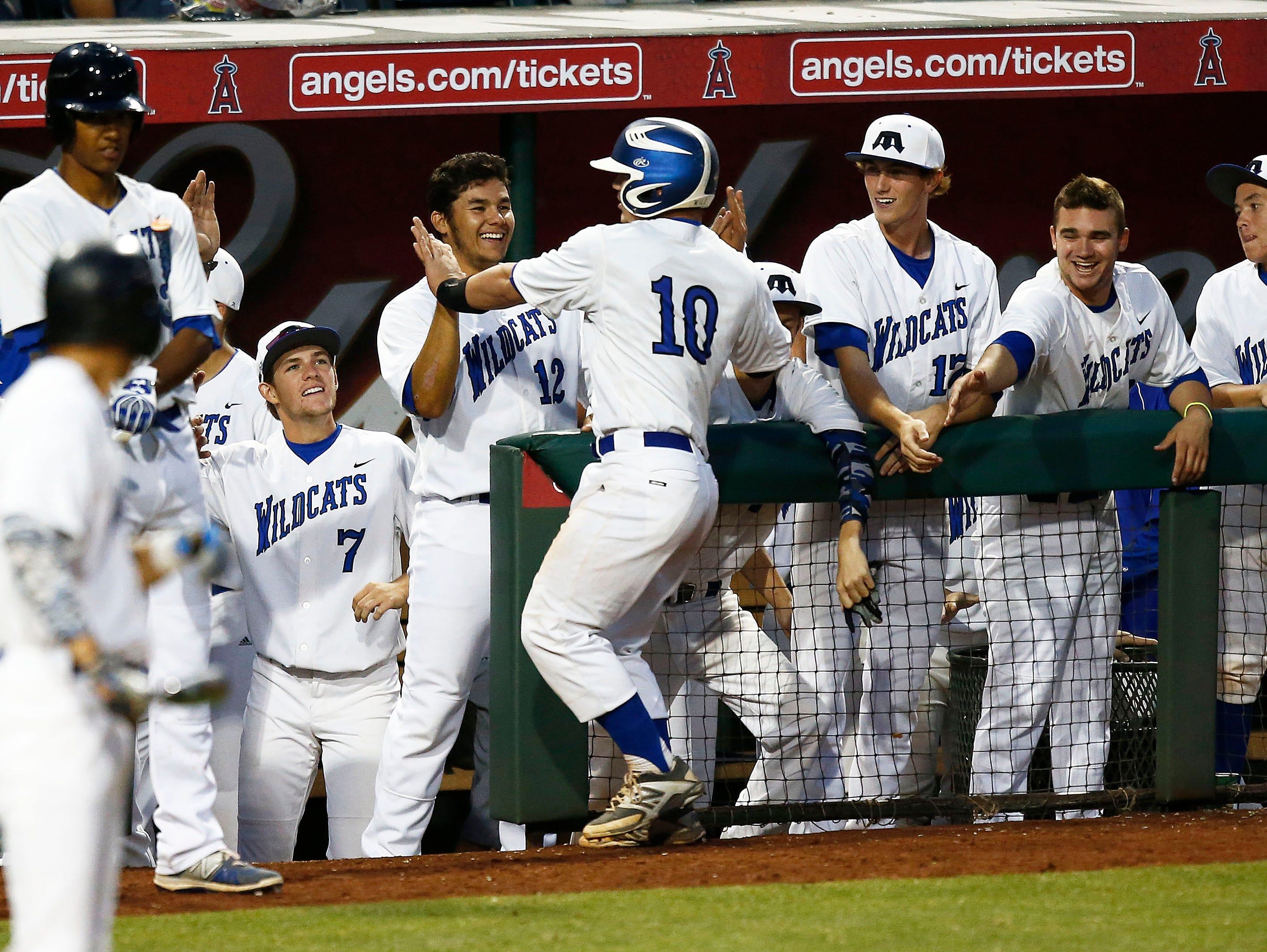 Brit Fitzgerald (10) of Gilbert Mesquite receives high-fives after hitting an RBI double against Glendale Mountain Ridge in the foiurth inning during the Division I state baseball semifinals on Thursday, May 14, 2015, at Tempe Diablo Stadium.