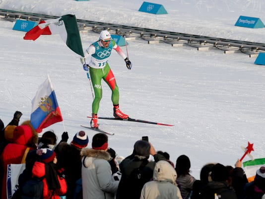 GermanMadrazo, of Mexico, holds up his countries flag after finishing last in the men's 15km freestyle cross-country skiing competition at the 2018 Winter Olympics in Pyeongchang, South Korea, Friday, Feb. 16, 2018.(AP Photo/Dmitri Lovetsky)