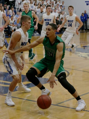 Oshkosh North High School's Quincy Anderson gets around Oshkosh West High School's A.J. Ambroso during their game.  Oshkosh West Wildcat boys hosted Oshkosh North Spartans on the Steven L. Randall Court Tuesday, December 8, 2017Joe Sienkiewicz / USA TODAY NETWORK-Wisconsin