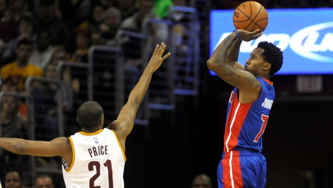 Detroit Pistons guard Brandon Jennings hits a three-pointer past the defense of Cleveland Cavaliers guard A.J. Price during the second half at Quicken Loans Arena. The Pistons won 103-80.