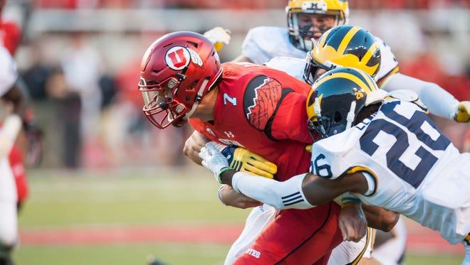 Utah quarterback Travis Wilson is tackled in the second quarter Thursday night.