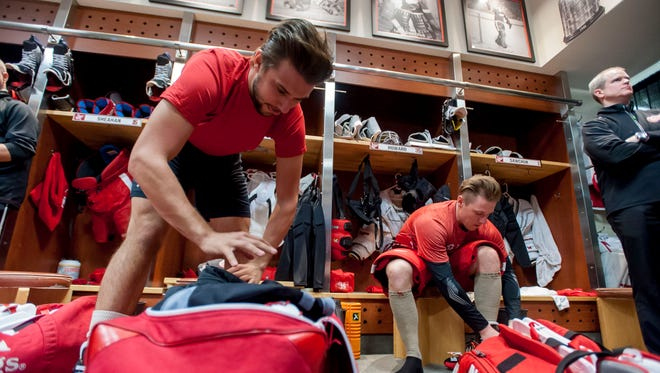 Goalies Petr Mrazek, left, and Jimmy Howard pack up their gear after the team photo was taken Monday.