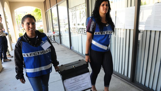 Election workers Silvia Trejo, left and Candace Messenger carry a full ballot box on Tuesday afternoon, June 7th, into the Monterey County Elections office in Salinas, CA.