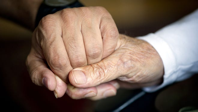 File picture - An elderly man holds the hand of his carer.