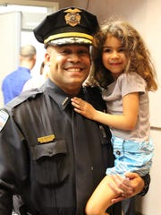 Alamogordo Police Chief Brian Peete takes a moment during the oath ceremony to hold his daughter, Gabriella.
