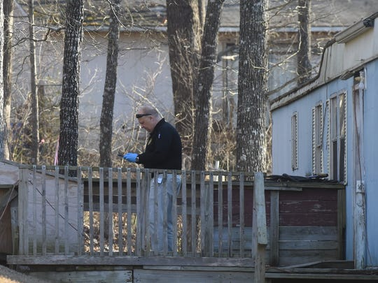 Baxter County investigator Scott Thrasher works at the scene of a Wednesday shooting.