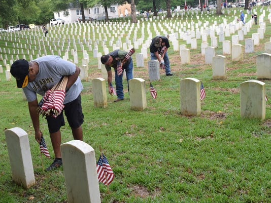 Henry Hurd (front), a retired U.S. Army veteran who served for 30 years, was among the many volunteers who helped place flags on the 7,816 gravesites at the Alexandria National Cemetery Saturday, May 26, 2018 in preparation for the Memorial Day program se
