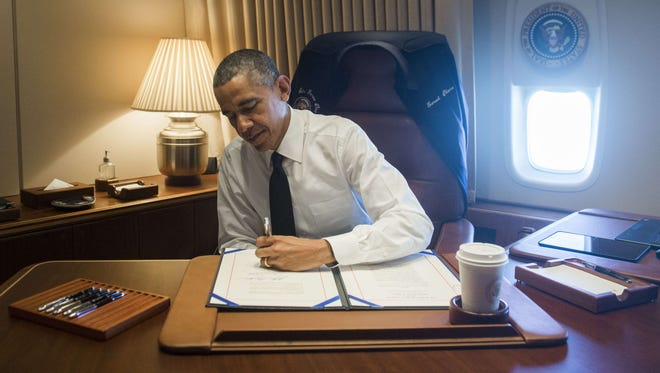 President Obama signs a bill that will give the Congressional Gold Medal to the foot soldiers who participated in Bloody Sunday in Selma, Ala, in his office aboard Air Force One as he flies to Alabama on March 7.