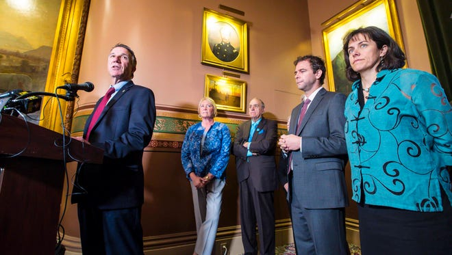 Gov. Phil Scott, left, Senate President Pro Tempore Tim Ashe, second from right, and Speaker of the House Mitzi Johnson, right, announce a new state budget and school employee health care deal at the Statehouse in Montpelier on Wednesday, June 21, 2017.