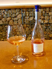 A bottle and glass of sparkling rose wine rests on