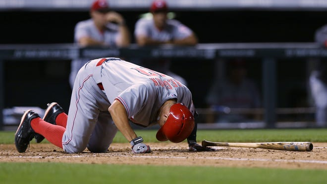 Cincinnati Reds' Kris Negron reacts after fouling ball off his foot while facing the Colorado Rockies in the sixth inning of a baseball game in Denver on Sunday, Aug. 17, 2014. Negron went on to single to conclude the at-bat. The game is being made up after it was postponed on Saturday by a water main break that left the stadium waterless.
