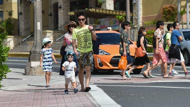 Tourists walk the streets of Tumon on Jan 4.