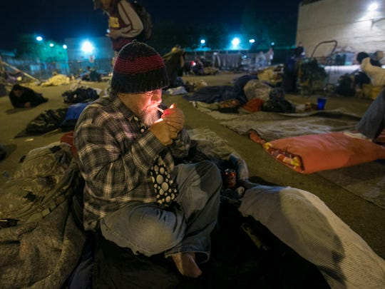 Terry Brooks, 50, lights a cigarette at the East Lot, which is Maricopa County's current solution for emergency shelter in Phoenix.