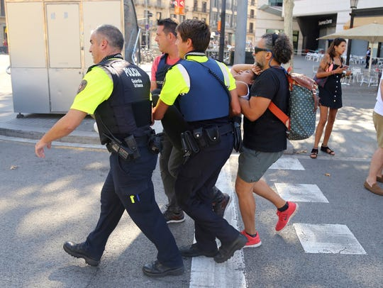 An injured person is carried in Barcelona after a white