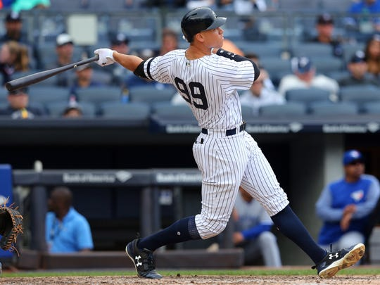 New York Yankees designated hitter Aaron Judge (99) follows through on a solo home run against the Toronto Blue Jays during the fourth inning at Yankee Stadium in the Bronx on Saturday, Sept. 30, 2017.