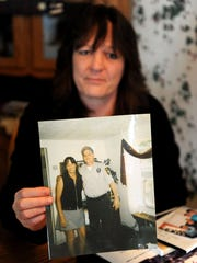 Jodie Lemaster holds up a photograph of her brother Mike to show what he looked like before dying of a drug overdose in 2007.