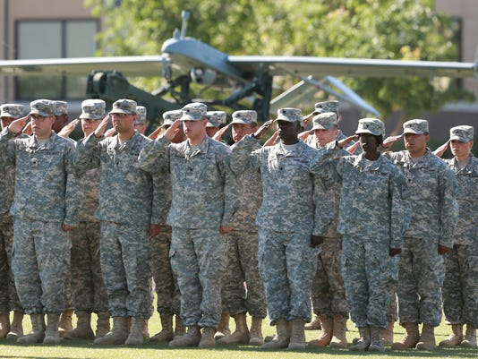 VICTOR CALZADA-EL PASO TIMES Soldiers from the re-flagged 40th Engineer Battalion salute during Wednesday's Reactivation ceremony. A drone and its launcher are in the  background.