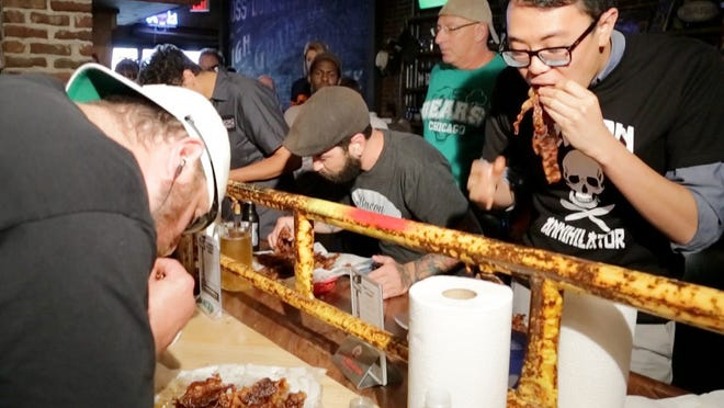 Journal & Courier reporter Wei-Huan Chen, right, takes on Todd Dotson, left, and others at the pop-up two-pound bacon challenge Friday at DT Kirby's in Lafayette. Todd Dotson won the event and was crowned champion after eating all two pounds.