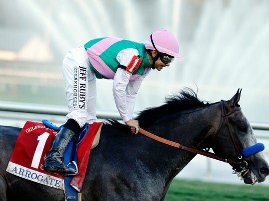 FILE - In this Jan. 28, 2017, file photo, jockey Mike Smith stands up in the saddle after riding Arrogate to win the inaugural running of the $12 million Pegasus World Cup horse race at Gulfstream Park in Hallandale Beach, Fla. Arrogate heads a full field of 14 horses for the Breeders' Cup Classic, one of five horses pre-entered in the $6 million race by Hall of Fame trainer Bob Baffert. (AP Photo/Lynne Sladky, File)