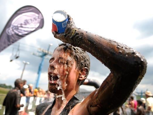 Xavier Pahl, 12, throws water on his face Saturday after his first participation at the Mudman race in Kimball. The course had many obstacles and many heats for participants to get plenty of mud on their faces and bodies.