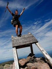 "Jesse Metzler, 19, of Newton, Ma., who goes by the trail name ""Sputnik,"" celebrates on the top of a sign marking the northern terminus of the Appalachian Trail at the summit of Mt. Katahdin in Baxter State Park, Maine, on July 19."