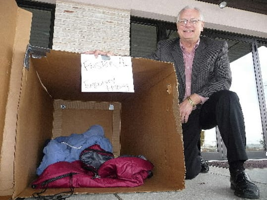 The Rev. Alan Smith, pastor of the Church of the Good Shepherd in North Cornwall Township, poses next to the cardboard box in which he sleeps outside of his church in this photo taken in late November. Smith is sleeping outside to raise money and awareness for a temporary homeless shelter in Lebanon.