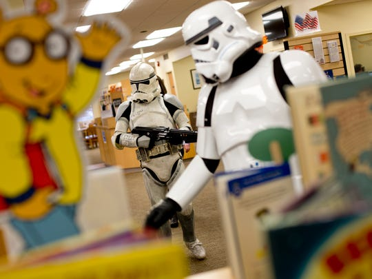 A Storm Trooper and Clone Trooper walk among bookshelves during a meet-and-greet with Star Wars characters Saturday, November 21, 2015 at the Marine City Public Library.