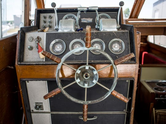A deteriorating ships wheel is seen in the cabin of