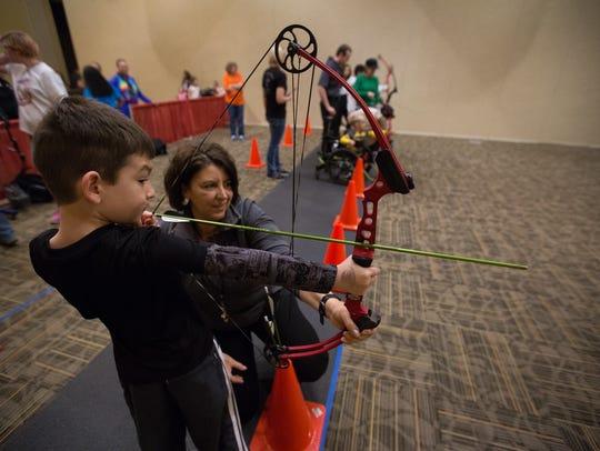"Carlos ""CJ"" Parra,7, draws an arrow back with help"
