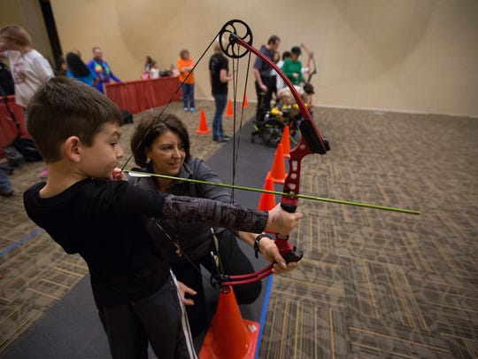 "Carlos ""CJ"" Parra,7, draws an arrow back with help and advice from Michaela Wolfe, with New Mexico Game and Fish, in the archery range at the Mesilla Valley Outdoor Expo, Saturday January 14, 2017 at the Las Cruces Convention Center."
