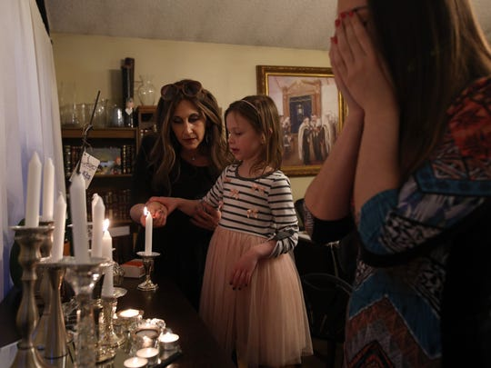 Bassie Friedman helps her daughter Devorah Leah Friedman, 6, light a candle during Shabbos as her son's girlfriend Miriam recites a blessing Feb. 16, 2018 in Pomona.