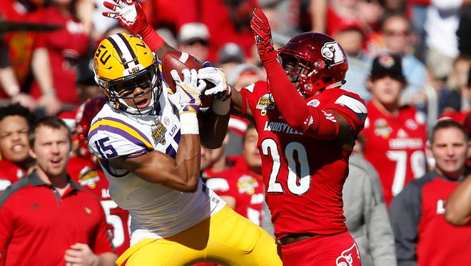 Dec 31, 2016; Orlando, FL, USA; LSU Tigers wide receiver Malachi Dupre (15) makes a catch for a first down as Louisville Cardinals cornerback Ronald Walker (20) defends during the first quarter of an NCAA football game in the Buffalo Wild Wings Citrus Bowl at Camping World Stadium. Mandatory Credit: Reinhold Matay-USA TODAY Sports